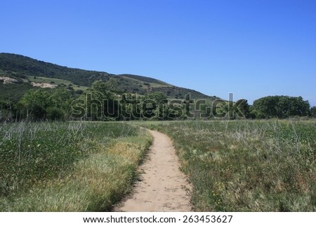 Trail leading through a field toward hills, California - stock photo