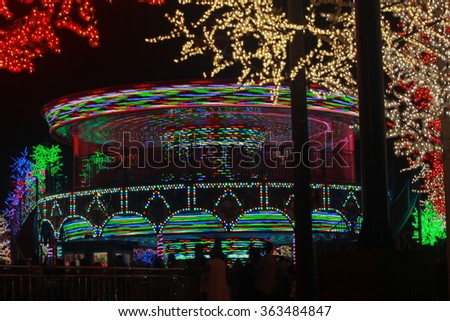 Trail light of a merry-go-round, a thrill ride in an amusement park, at night, with a dark black background. - stock photo