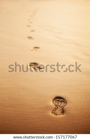 Trail of human footprints on the beach at sunset. Selective focus. - stock photo