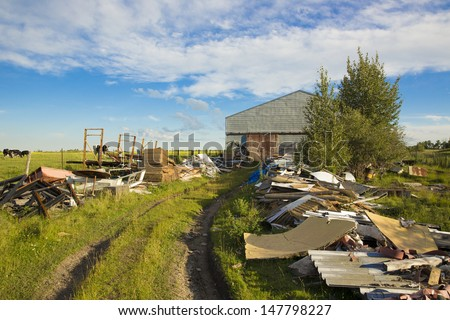 Trail of junk or collectibles on the way to a large shed - stock photo