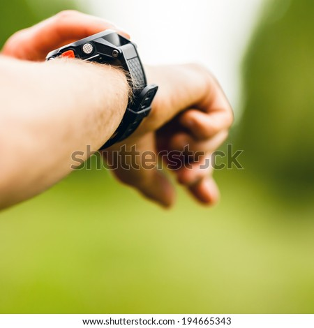 Trail or cross country runner on mountain path looking at sportwatch smart watch, checking performance or heart rate pulse. Goal achievement, sport and fitness concept outdoors in nature. - stock photo