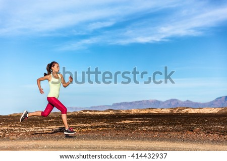 Trail runner female athlete running in nature rocky mountain background. Active fit sports woman in red capris and sportswear sprinting on rocks path working out cardio training body. - stock photo