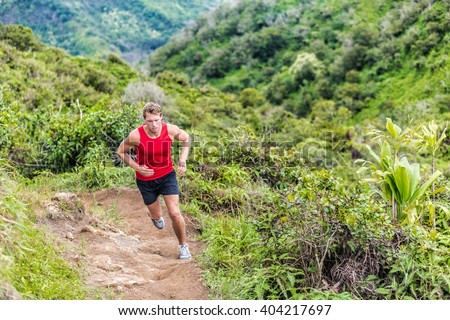 Trail runner running in summer mountain nature landscape on difficult path in mountains in summer wilderness. Athlete jogger working out cardio going up on cross country race uphill outdoors. - stock photo