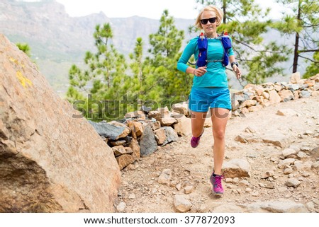 Trail runner woman cross country running in mountains, inspirational landscape. Training and working out runner jogging and enjoy outdoors in nature, rocky footpath on Canary Islands, Spain - stock photo
