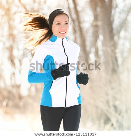 Trail running in winter. Woman fitness sport runner training outside cold winter forest path. Happy Caucasian / Asian girl in her twenties. - stock photo