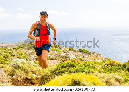Trail running man, happy cross country runner in inspirational mountains landscape on beautiful day. Training and working out person jogging fitness and exercising, rocky footpath on Crete, Greece - stock photo