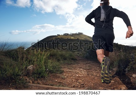 trail running man on mountain path exercising - stock photo