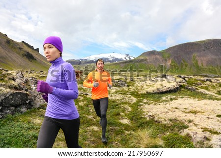 Trail running people in cross country run. Woman and man runners training jogging outdoors in beautiful mountain nature landscape on Snaefellsnes, Iceland. - stock photo