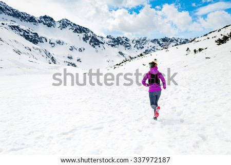 Trail running woman runner in white winter mountains on snow. Motivation and inspiration fitness concept with beautiful inspirational landscape. Active accomplish runner training outdoors in nature. - stock photo