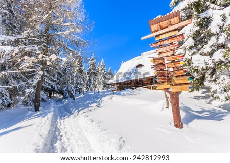 Trail sign with directions and wooden mountain hut on path in snow to Turbacz in winter landscape of Gorce Mountains, Poland - stock photo