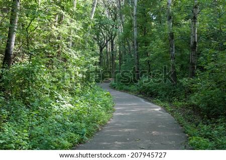 Trail winding through Marthaler Park forest in West Saint Paul Minnesota - stock photo