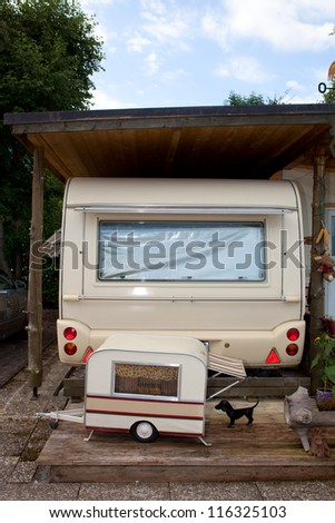 Trailer camp under a shed  with smaller trailer and a dog visible in the foreground. - stock photo