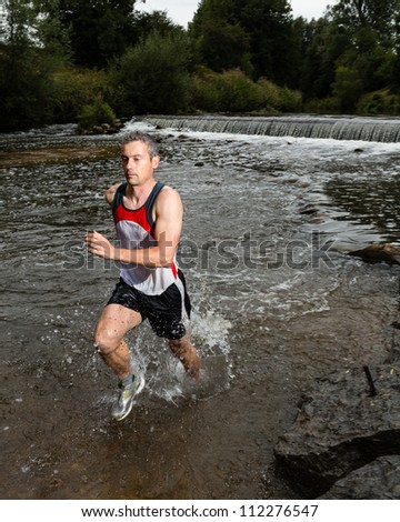 trailrunner with splashing water - stock photo