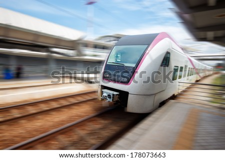 Train approaching railway station with motion blur. - stock photo