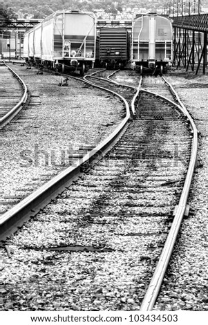 Train freight cars parked and waiting for dispatch on steel rail tracks in a transportation railway line depot railroad yard - stock photo