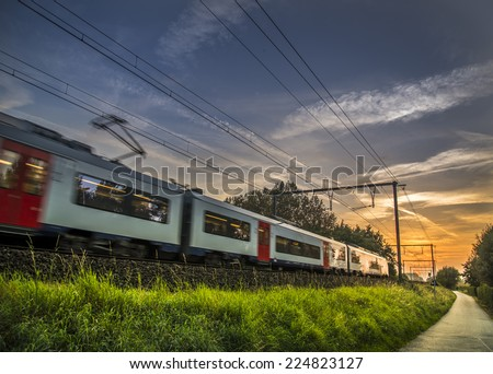 Train heading for an amazing sunset - stock photo