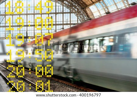 Train in blurred motion leaving a station, with departure times in foreground - stock photo