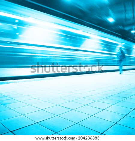 Train in motion blur and blurred commuter walking in subway station.   - stock photo