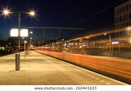 Train leaving a Dutch train station  in Groningen in the evening. - stock photo