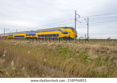 Train moving through the countryside in winter - stock photo