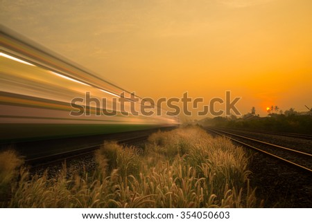 Train Passing by over Rural Railway Bridge in the Morning or at Dawn with Sunrise - stock photo
