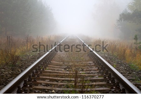Train rails in foggy weather in Poland - stock photo