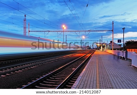Train station in motion blur at night, railroad - stock photo