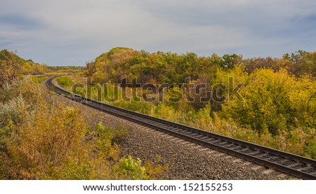Train track covered with fallen leaves in autumn - stock photo