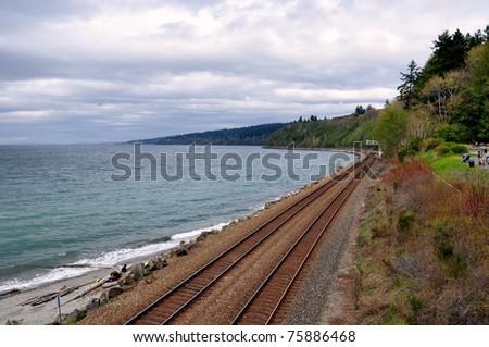 Train tracks along the coastline receding into the distance - stock photo