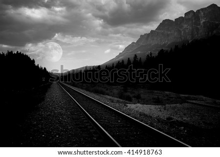 train tracks in a remote area with mountains and a full moon in a background in black and white - stock photo