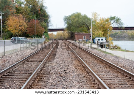 Train tracks leading out of a small rural town disappear around the bend past trees covered in fall leaves - stock photo