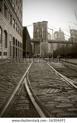 Train tracks on cobblestone road in Dumbo area of Brooklyn, Brooklyn Bridge tower in background, black and white. - stock photo
