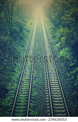 Train tracks with the natural landscape and sunset - stock photo