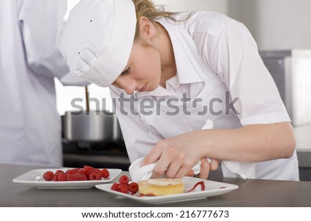 Trainee chef wiping plate of gourmet dessert in commercial kitchen - stock photo