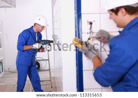 Trainee electricians learning their trade - stock photo