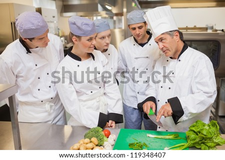 Trainees learning vegetable slicing in the kitchen - stock photo