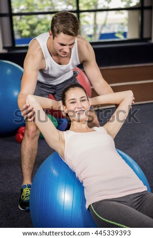 Trainer assisting a woman doing abdominal crunches on fitness ball at gym - stock photo