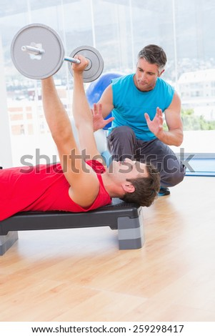 Trainer assisting man with dumbbells in fitness studio - stock photo