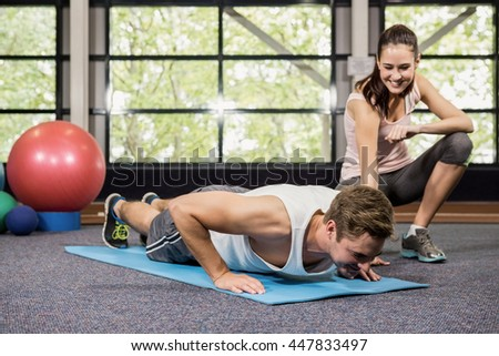 Trainer assisting man with push ups at gym - stock photo