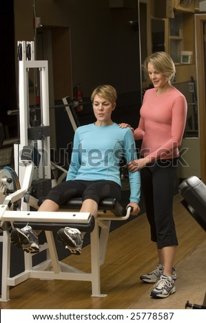 Trainer assists client during workout - stock photo