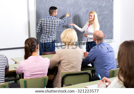 Trainer coaching empoyees at a business training in a class room - stock photo
