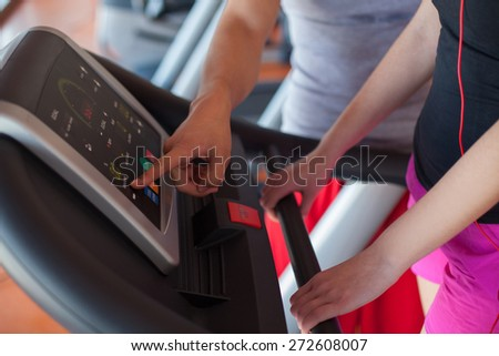 Trainer explains to a young woman how to use treadmill in fitness club - stock photo