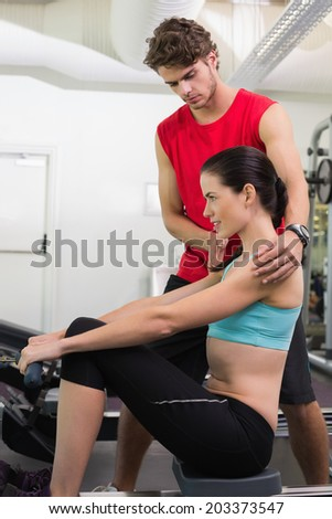 Trainer helping his pretty client on the rowing machine at the gym - stock photo