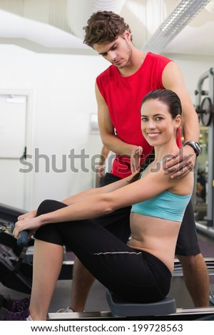 Trainer helping his smiling client on the rowing machine at the gym - stock photo