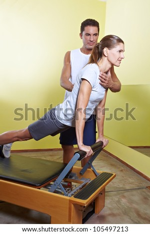 Trainer helping woman with posture correction in fitness center - stock photo