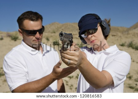 Trainer helping young woman to aim with handgun at combat training - stock photo