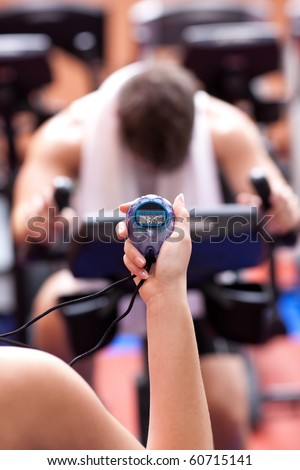 trainer holding a chronometer while man doing physical execice on a bicycle - stock photo