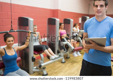 Trainer in weights room with women in gym - stock photo