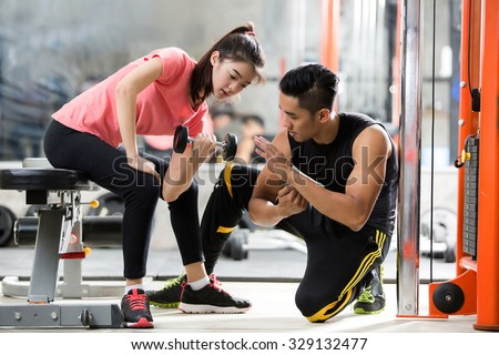 Trainer men are teaching Asian woman lifting a dumbbell. In the way they exercise in the gym. - stock photo