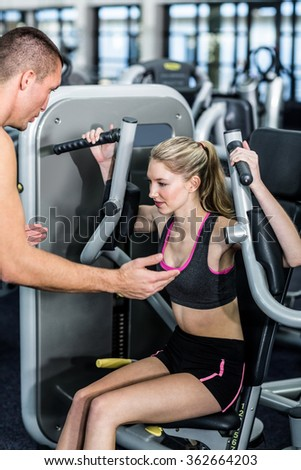 Trainer motivating woman while using exercise machine at the gym - stock photo